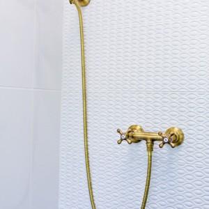 Detail vzorkové koupelny v koupelnovém studiu Gremis - sprcha, imitace zlata
