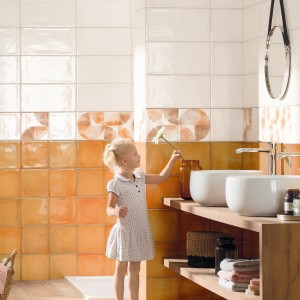 Inspirace koupelnami Rako - dítě v bílo oranžové koupelně