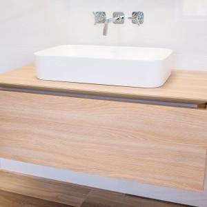 Detail vzorkové koupelny v koupelnovém studiu Gremis - umyvadlo na dřevěné platformě