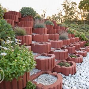 Červená dlažba Ferobet k dostání v obchodě Gremis, příklad použití v terasovitých květináčích
